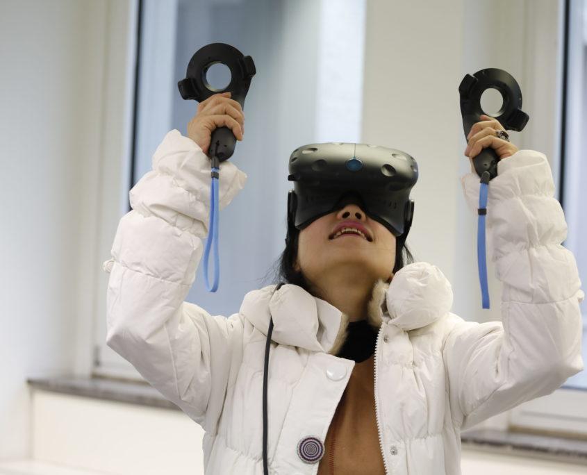 Frau trägt VR Brille und VR Controller