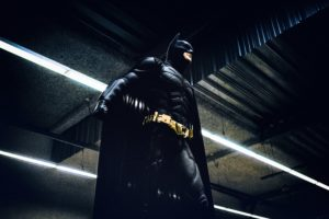 Wie schreibt man ein Drehbuch? Batman steht vor schwarzem Hintergrund und Neonröhren