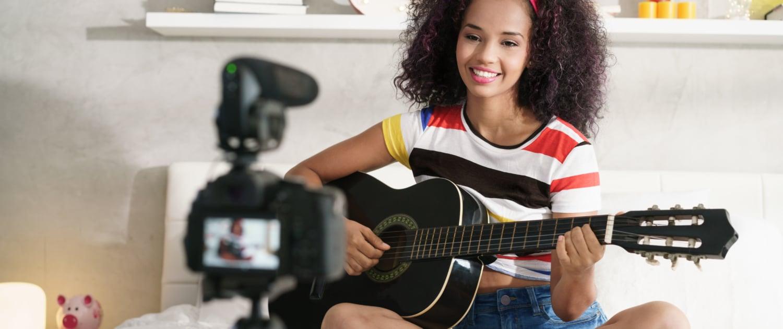 Influencerin spielt Gitarre vor der Kamera