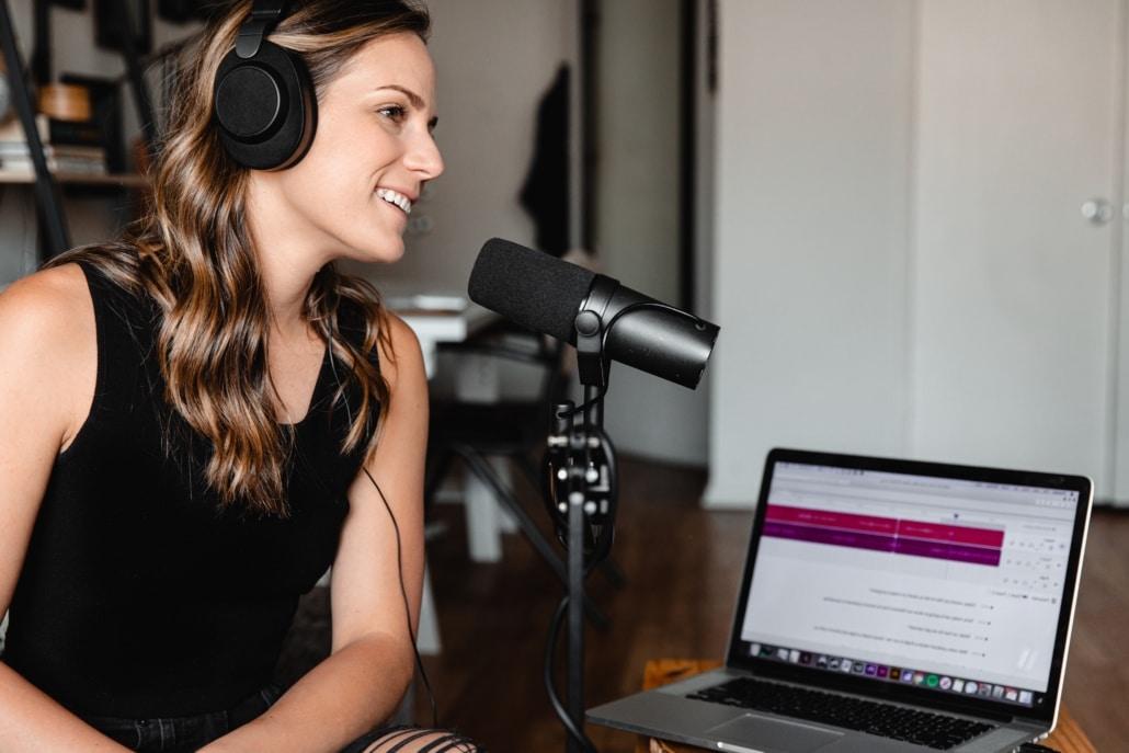 Frau mit Kopfhörern und Mikrofon vor Laptop spricht Podcast ein Podcast Produktion Frankfurt