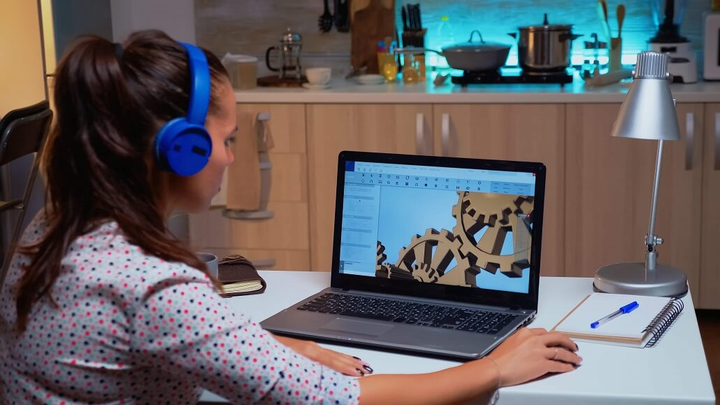 Frau mit Kopfhörern arbeitet an Laptop mit 3D Animationssoftware