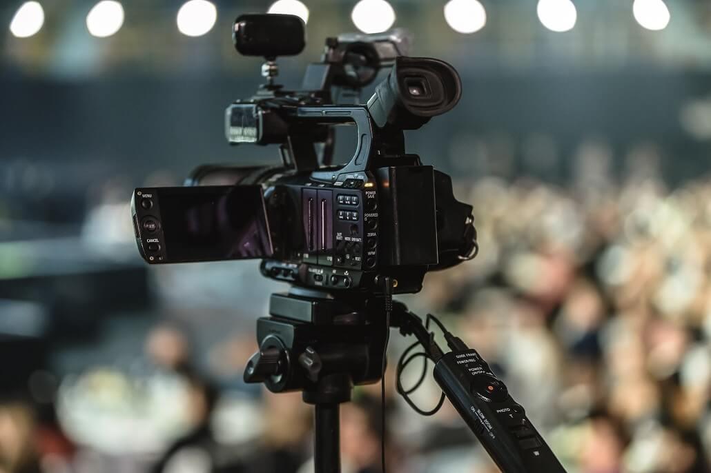 Eine professionelle Kamera wurde zum Aufnehmen eines hybriden Events aufgestellt.
