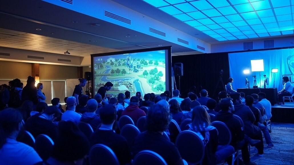 Das Publikum einer Hybridveranstaltung sitzt vor einer Bühne und einem großen Display