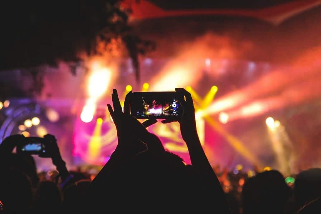 Zuschauer filmt mit einem Smartphone die Bühne eines hybriden Events