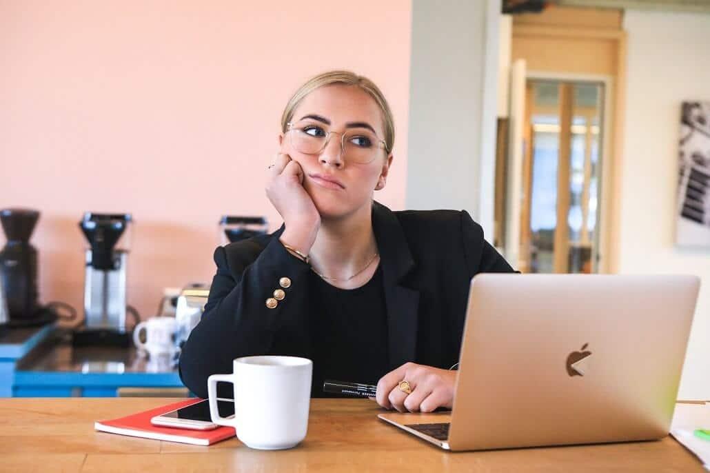 Frau am Schreibtisch überlegt, um die richtige Erklärvideo Agentur für Ihr Unternehmen zu finden.