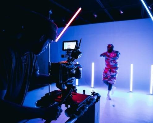 Das Thumbnail unseres Videoproduktion Anbieter Vergleichs zeigt einen Kameramann, der vor einem blauen Hintergrund ein Video aufnimmt.
